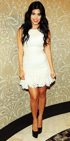 Kardashian hosted an engagement party for her sister Kim sporting a white pleated minidress and sky-high patent pumps.