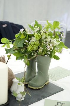 rain boots used as containers for garden style flower arrangement