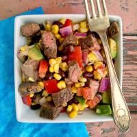 Cuban Style Steak and Corn Salad - Chuck tender steaks are infused with a Cuban style marinade and grilled, sliced, and placed on top of a Cuban inspired corn and black bean salad.