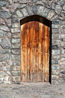 Image of 'old wood door in a stone wall of an ancient building of an abandoned mountain village'