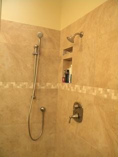 bathroom shower with carmel colored atlas travertini tile in an 18x18 the wrap is a