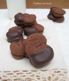 frollini al cacao defper la frolla montata: 250 g di farina 00 250 g di burro morbido 70 g di zucchero a velo 25 g di cacao amaro 35 g di cioccolato fondente al 70% 40 g di albume 1/2 bacca di vaniglia bourbon  per la finitura: 100 g di crema di nocciole (ho usato la Novi) 100 g di cioccolato fondente al 50% di cacao
