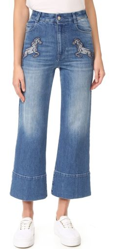 denim flared cropped jeans by Stella McCartney. Horse appliqués add a playful feel to these cropped Stella McCartney flares. 5 pocket styling. Button closure and zip...