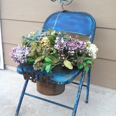 Found a vintage metal folding chair, cut a hole in the seat, added a rusty paint can, a bird and a welcome sign. Great planter!!