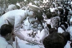 King Bhumibol Adulyadej receiving garlands from villagers .