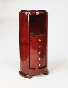 """Art deco cylindrical cabinet done in loupe d'amboine onto a solid mahogany frame inlaid in ivory """"fileté"""" and ivory handles designed by Christian Krass. The cabinet has 5 small drawers and a display niche with a gilded pebble glass bottom Made in France Circa: 1935"""