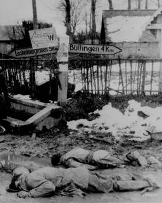"""American soldiers, stripped of all equipment, lie dead, face down in the slush of a crossroads somewhere on the western front."" Captured German photograph. Belgium, ca. December 1944."