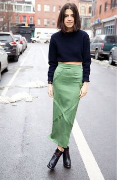 Leandra Medine wears a green satin midi skirt with a cropped black sweater and black booties.