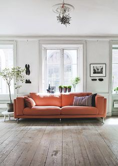 living room with tall white ceilings with medallion and orange modern sofa / sfgirlbybay