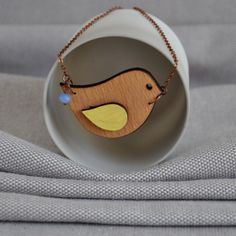 Origami Bird Necklace by ArtySmartyShop.com  This origami style necklace is made from birch wood, carefully hand painted in pastel colors and finished with a durable varnish. The chain is an vintage style antiqued copper with a lobster clasp, glass bead and 'artysmarty' rabbit tag. There are also matching brooches in this series.  #artysmarty #fashionbloggers #accessories #womenswear #unique #handmadejewelry