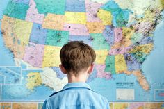 Boy stands looking at a map of the United States by Cara Slifka