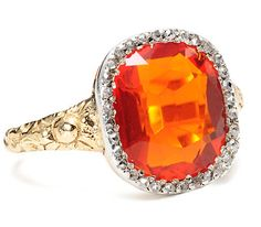 An oval faceted fire opal of an estimated 3.0 carats dominates this circa 1920 ring with its very fine and clear orange-red hue. The color is exceptional, not at all cloudy or muddy and the true intensity of such a gem shows. A surround of thirty-one (31) tiny rose cut diamonds and one single cut all set in silver caresses the passionate stone with an intense embrace. An antique base and shank of 14k yellow gold adorned with a swirling floral motif have been added.