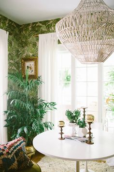 Timeless Scandinavian white pedestal dining table with white open-weave pendant lantern and leafy Beverly Hills Hotel-inspired green banana leaf print wallpaper on the walls.
