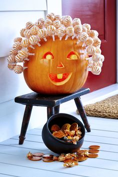 """Hollow out medium round pumpkin from the bottom. Carve half-circle mouth with a tooth, 2 half-circle eyes with pupils and triangle nose. For eyes, push in inner piece (don't remove). Then, etch away skin on pupils and tooth with linoleum cutter. Use awl to poke holes about 1½"""" apart across top and sides of pumpkin. Push lollipops (Orange Sassy Suckers, $25 for 100; candywarehouse.com) into holes to create hair."""