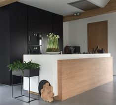 Black white and wood kitchen with long monolithic central island