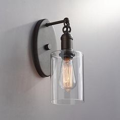 A rich bronze finish enhances the industrial look of the Cloverly iron wall sconce.