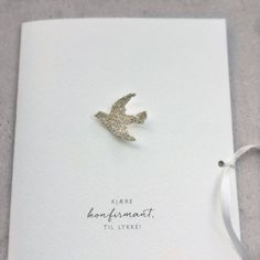 Kort til konfirmant med håndlaget fugl i sølv og bånd av ekte, matt silke.