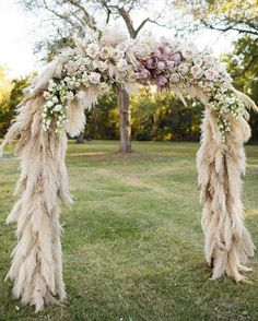 """We were trying to keep it bohemian and natural but greenery doesn't really pop in an outdoor ceremony in a green field with green trees in the background,"" planner and designer Julie Savage Parekh of Strawberry Milk Events says of the ceremony arch. So pampas grass covered the structure, which was topped with groupings of flowers. 