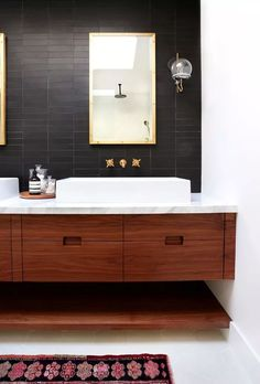 Love this handsome and modern master bathroom, complete with floating wood cabinets, matte black tiles, brass hardware and white carrara marble countertops. Trendy Bathroom, Modern Master Bathroom, Bathroom Trends, Amber Interiors, Bathroom Vanity, Modern Bathroom, Bathrooms Remodel, Bathroom Design, Tile Bathroom