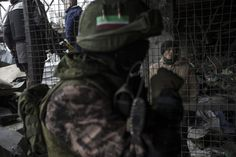 A Ukrainian war prisoner (R) is guarded by armed men of the separatist self-proclaimed Donetsk People's Republic army in the Donetsk airport, February 26, 2015. REUTERS/Baz Ratner
