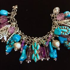"""Navajo Turquoise Amethyst .925  Charm Bracelet Navajo Seeping Beauty Turquoise Amethyst squash Blossom Charm Sterling Silver Bracelet an amazing showstopper of a bracelet that will dazzle and enchant. Artisan designed and handcrafted, this is a one of a kind exclusive bracelet. Measures 7.5"""" in length. Made with quality vintage Navajo charms stamped """"Sterling"""" on back, soldered on a .925 double link bracelet with push clasp and safety chain. Unbelievably gorgeous and unique! Vintage Jewelry…"""