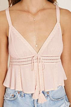 In crinkled woven crepe, this sleeveless crop top features a V-neckline, a V-cut back, crochet panels on the front, and a tasseled self-tie accent.