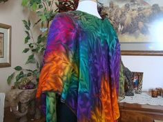 This gorgeous multi colored streaked poncho is hand painted and is 100% silk. Hand hemmed as well. Lovely mixture of many colors dripping into each other to create a lovely picture for you to wear with your favorite outfit. Imagine this with a Winter White outfit!! I challenge you to