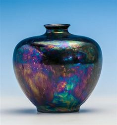 A Ruskin iridescent vase of squat ovoid form, short flared neck, supported on raised circular foot, impressed mark to base 'Ruskin England 1919', 4 1/4in. (10.8cm.) high, 4 1/2in. (11.5cm.) diameter.