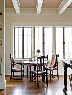 In a kitchen dining area, an antique table and chairs sit in front of the old casement windows, with wavy glass. Design: Mary Jo Bochner