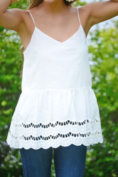 The prettiest white tank around! Eyelet and a scalloped hem give it plenty of standout details. Tank also has a slim back cutout that buttons at the top. Fabric is a lightweight cotton-blend.