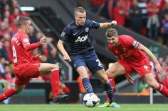 Tom Cleverley of Manchester United in action with Iago Aspas (L) and Steven Gerrard of Liverpool