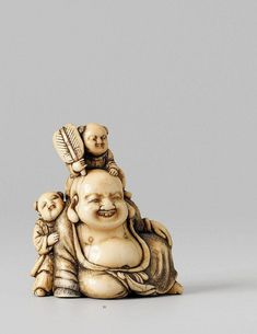 A superb Kyoto school ivory netsuke of Hotei with two karako, by Okatomo. Late 18th century. Seated and smiling contently, the crosshatched robe falling open to reveal his ample belly, while a karako with a fan clambers over his head and another karako holds his arm out to offer a leg-up to his companion. Signed Okakoto in a rectangular reserve. Very good and shiny patina.