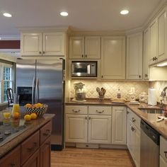 Love this kitchen-- cream cabinets, tile backsplash, wood floors. This would totally fit in my house. :)