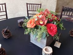 Orchids, roses and seeded eucalyptus for a warm and rustic centerpiece.