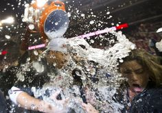 Washington Nationals first baseman Adam LaRoche is doused as he is interviewed by a television reporter, right, during the Nationals' celebration after clutching the National League East division title following their baseball game against the Philadelphia Phillies in Washington on Oct. 1, 2012. (Photo: Manuel Balce Ceneta / AP) #Baseball