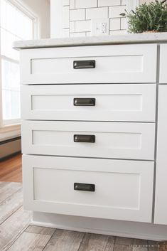 white kitchen cabinets with squared cup pulls featuring hickory hardware oxford antique cup pulls and manchester knobs via