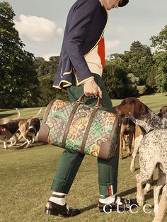 Shot on the grounds of Chatsworth, hounds together with a look from the men's Gucci Cruise 17 collection—piped-edged jacket, intarsia knit, pants, Queercore shoes and Gucci Bengal duffle.