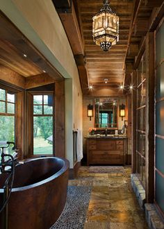Let us just examine the details here...beefy wood trim, rustic stone tile floors, wood on ceiling NOT walls, and the neutral walls with a soft patina.  Copper and oil rubbed bronze accents.  You can copy this for less.
