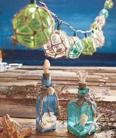 """The Seaside Home Decor collection will remind you of your last vacation at the shore. The Set of 2 Glass Bottles with Shells (approx. 2-1/8"""" sq. x 7-1/4""""H, each) features sand-filled bottles in different shapes with jute and seashell accents and a seashe"""