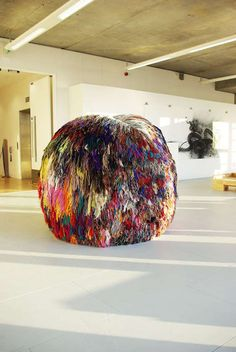 In artist Eleanor Davies' piece titled Over 200 Beautiful Colors, she crafts a traditional yarn pom pom (like something you'd see on a beanie), but on steroids. Using wool, newspaper, and rope, Davies wraps donut-shaped discs with yarn and stacks them on top of one another. They become a moun