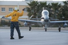 Aviation Boatswain's Mate (Equipment) Airman Adrian Brown, assigned to U.S. Naval Support Activity Souda Bay Air Operations Department Transient Line Division, directs an A-29 Super Tocano following its arrival.