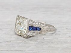 Art Decoengagement ring made inplatinumand centered with an approximate 3.05 caratEGL certified bezelset old european cut diamond with K-L color and SI2 clarity. Accented with calibre cut sapphires and single cut diamonds.Circa 1920 Unique Art Deco box set solitaire with stunning sapphire accents and fine millegrain filigree around the edges. This ring is unique and makes a beautiful and elegant statement. Diamond and gold mining has caused devastation in areassuch as Africa…