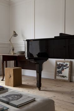 William Smalley flat in Bloomsbury, wood floors, white paneled walls, black grand piano | Remodelista