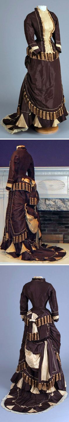 "Dress, circa 1880s: dark brown taffeta, cream silk damask, lace, and silk. Chester County (PA) Historical  Society: ""This dress is an example of over-the-top embellishment. It features silk chenille fringe, bows, lace, swags, ruffles and pleated scallops. There is even asymmetrical lacing up one side. What is even more astounding than the level of decoration is the size of the waist which measures merely 17.5"" around."
