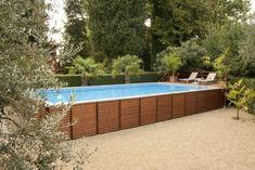 une piscine hors sol rectangulaire en bois et deux chaises-longues