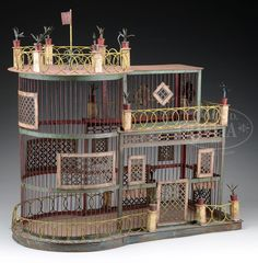 VICTORIAN WIRE BIRD CAGE IN THE FORM OF A STEAMBOAT. Third quarter 19th century, Southern region of America. This whimsical folk art example depicting a fantasy steamboat form of three decks with scrolling rails alternating with posts each mounted with potted shrubbery with latticework windows and ornamentation throughout. The circular front mimicking the bow and bridge of steamboat. The whole surmounted with flag on s scrolled wrought iron base. Painted in red, white and blue surfaces which…