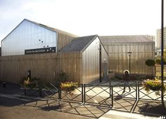 Les Coccinelles Nursery in France has a wooden facade that dapples sun and light in Saint-Gratien France