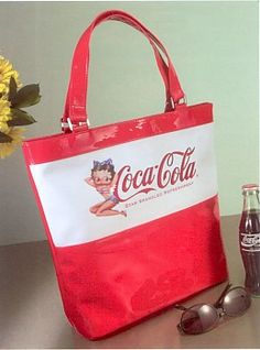 """Coca Cola and Betty Boop Star Spangled Refreshment Tote Bag features Betty Boop in a very patriotic red white and blue bathing suit. The bag reads """"Coca-Cola Star Spangled Refreshment."""