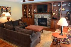 Living room with brown sectional sofa, stone fireplace and built-in shelving
