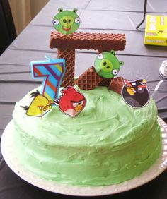 DIY Angry Bird Cake. (this is the cake I made) Make a double layer cake in flavor of your choice w/frosting of your choice (use food color for desired color). Use Nutty Bars as crates & print sm. pictures of Angry Birds & Pigs on paper. Glue pic's to toothpicks and place on top of cake.